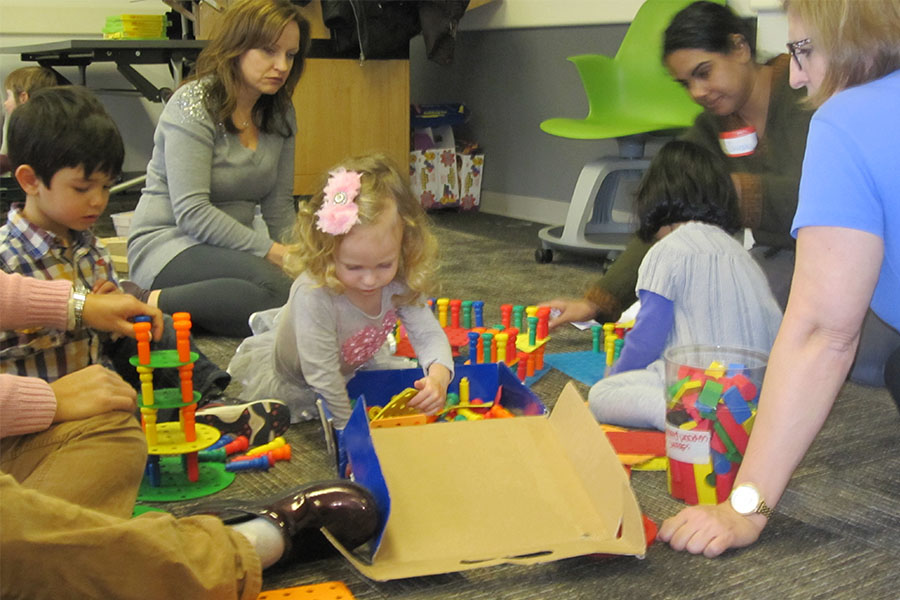 three year olds playing with blocks with adults