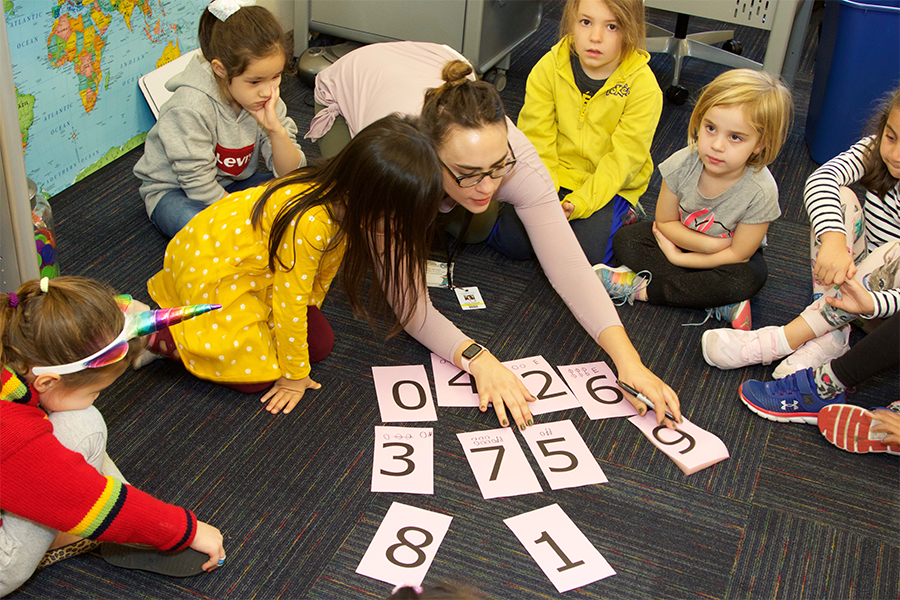 teacher with group of early childhood students playing math game