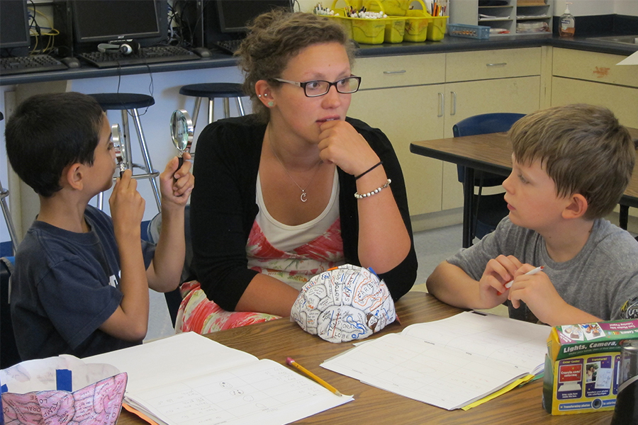 teacher talking with two young students