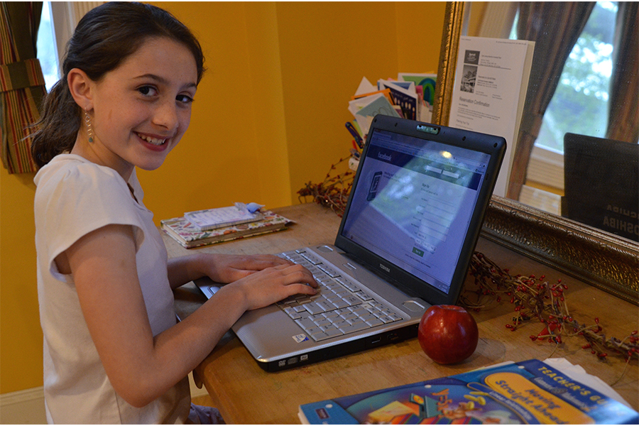 elementary school girl working on laptop at home