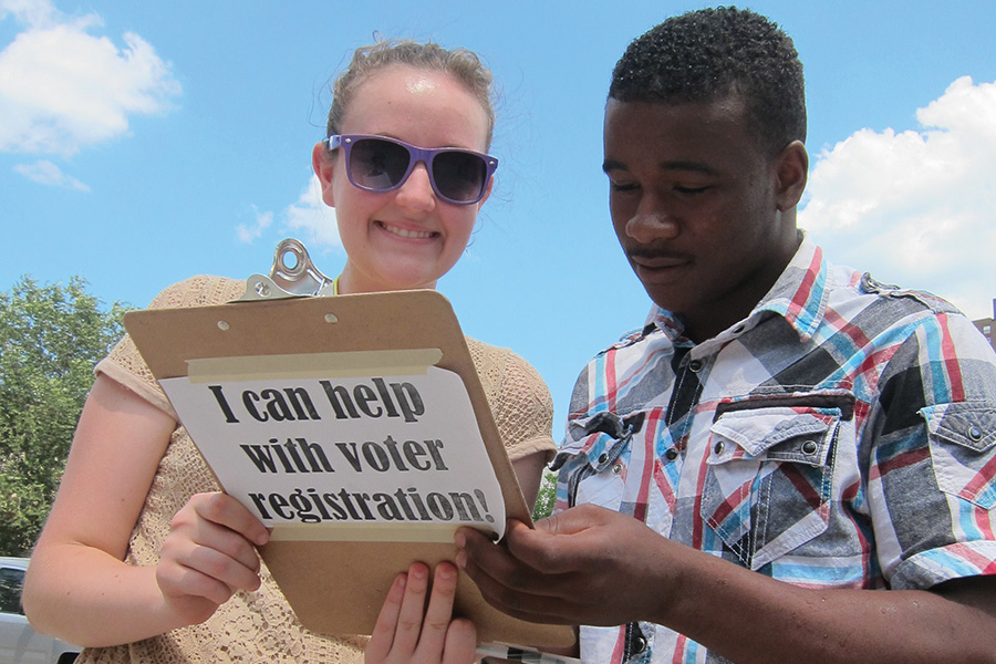 boy and girl holding clipboard for voter registration