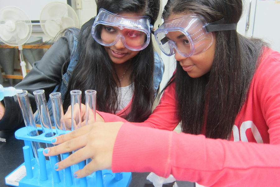 two girls in science lab conducting experiment