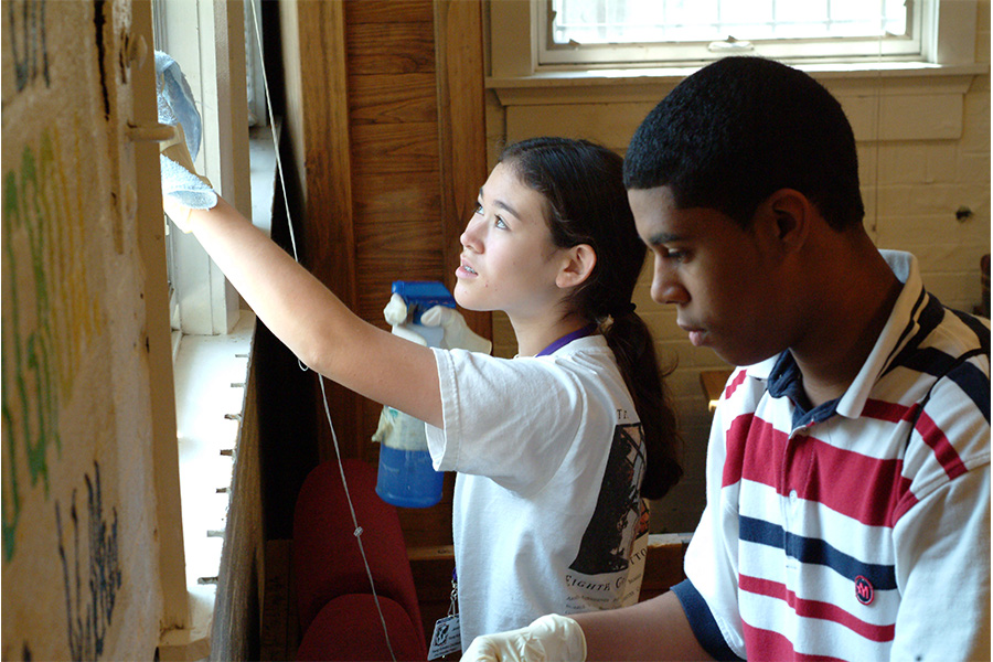 two young people cleaning windows