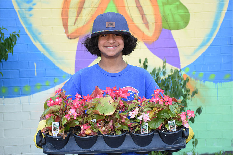 middle school boy holding plants in front of a mural