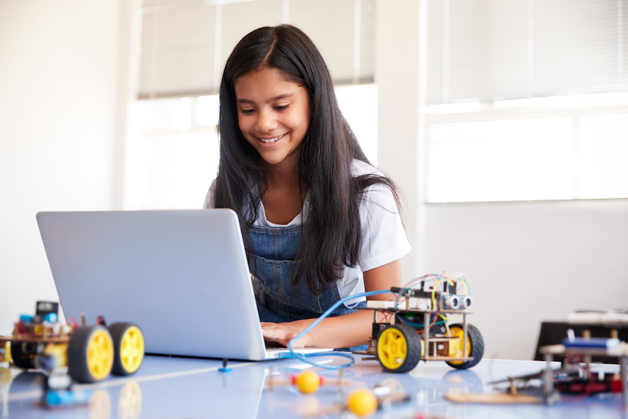 middle school girl at home on computer with robot