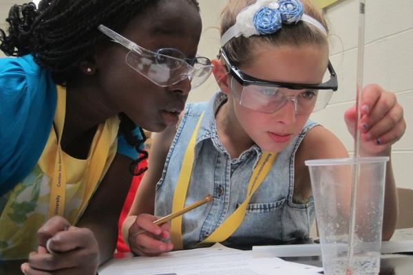 two elementary school girls close up doing a lab experiment