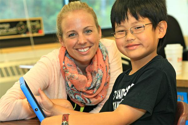 teacher and young boy with ipad smiling at camera